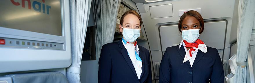 Kapitänin und Senior Cabin Attendant empfangen die Gäste beim Flugzeugeingang mit Gesichtsmaske